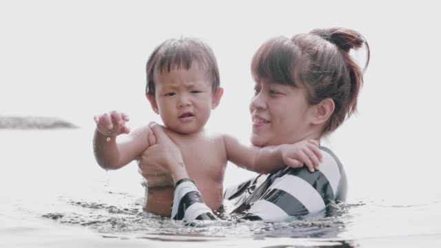 asian mother and child having fun in pool - 6 11 months stock videos & royalty-free footage