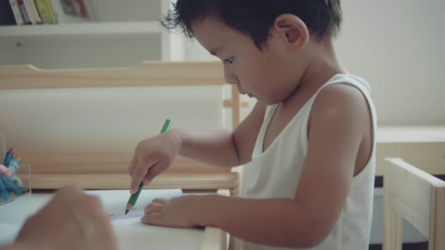 asian mother and child making greeting card for mothers day on the table in room at home. bangkok, thailand. - greeting card stock videos & royalty-free footage