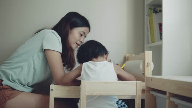Asian mother and child making greeting card for mothers day on the table in room at home. Bangkok, Thailand.
