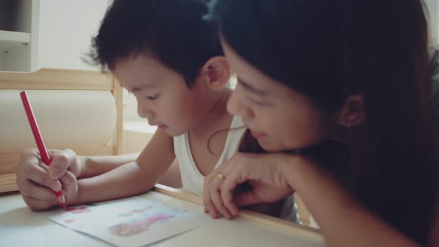 asian mother and child making greeting card for mothers day on the table in room at home. bangkok, thailand. - mother's day stock videos & royalty-free footage