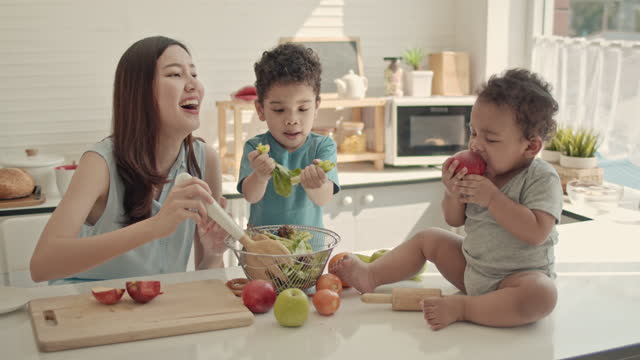asian mother and child preparing salad in the kitchen,slow motion - freshness stock videos & royalty-free footage