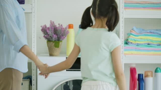 stockvideo's en b-roll-footage met aziatische moeder en kind wassen kleren. moeder en dochter hebben tijd om samen schoon te maken thuis. - clean