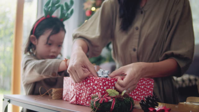 asian mother and child's assistance wrapping christmas gifts. - gift box stock videos & royalty-free footage