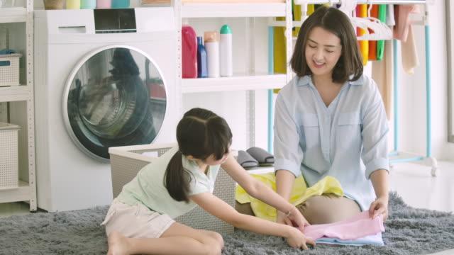 vidéos et rushes de mère asiatique et fille coupée laver des vêtements. - femmes d'âge moyen