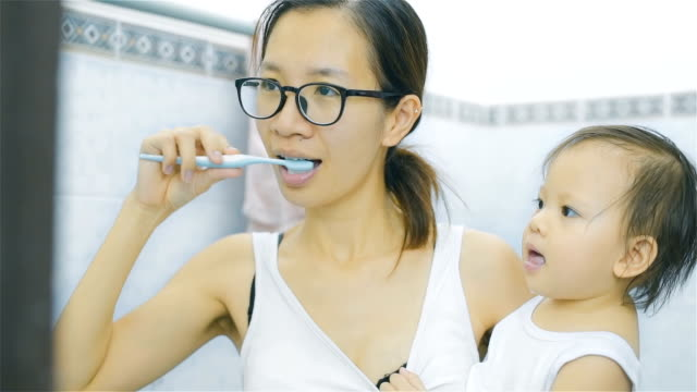 asian mother and daughter brushing teeth in bathroom together - igiene dentale video stock e b–roll