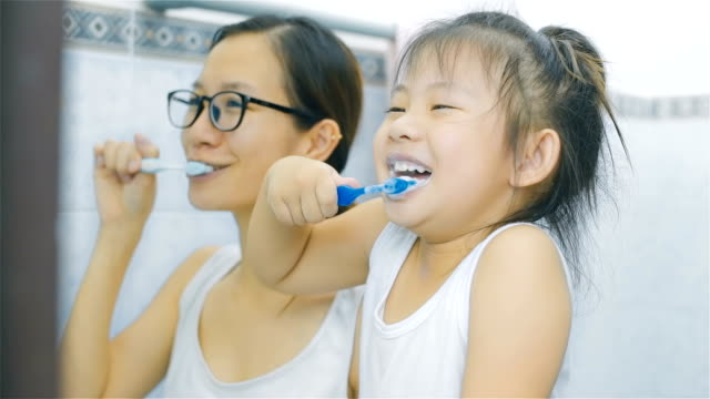 Asian Mother and daughter brushing teeth in bathroom together
