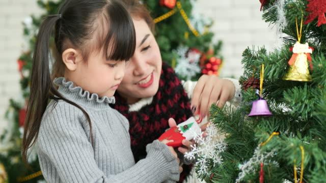 vidéos et rushes de la mère et la fille asiatiques décorent un arbre de noël ensemble. - famille monoparentale