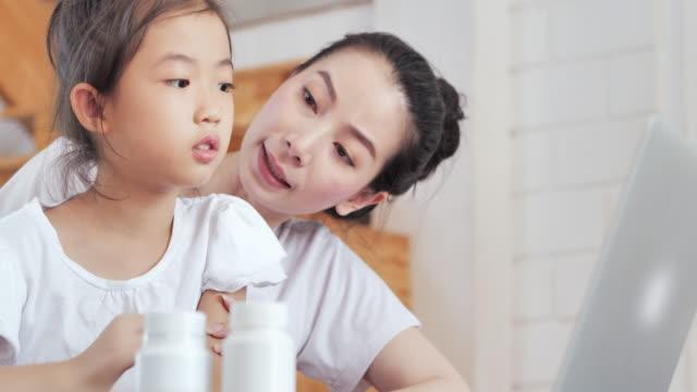 アジアの母と娘はピルボトルを見て、自宅でのビデオ会議に相談薬で薬を説明するアジアの女性薬剤師に耳を傾けます。家族, ビデオ通話, 子供, 技術, 医療, 医療, 教育, 医学とヘルスケア - 予防点の映像素材/bロール