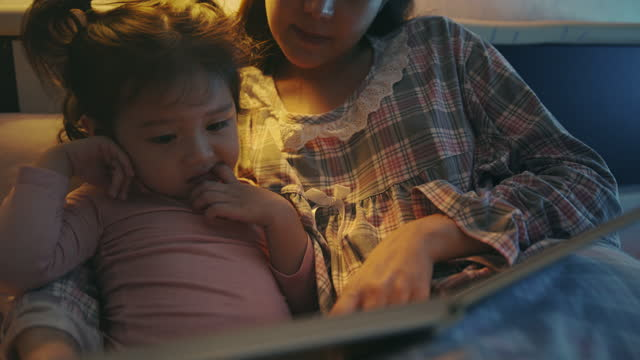 asian mother and daughter reading book and pointing to a book at home in the bedroom. bedtime story - storytelling stock videos & royalty-free footage