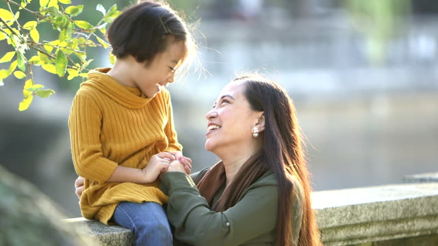 Asian mother and daughter talking, laughing
