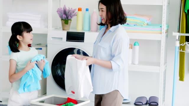 asian mother and daughter use washing machine - 家事点の映像素材/bロール