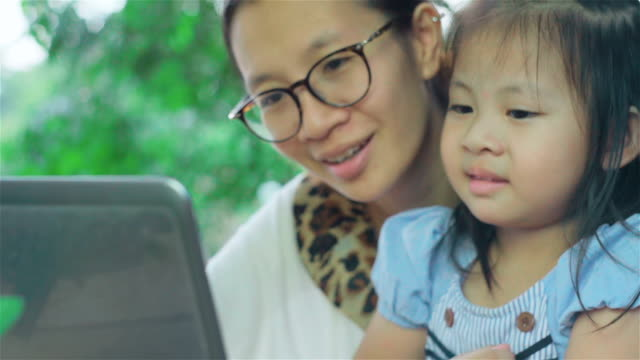 asian mother and daughter using laptop at the garden - netbook stock videos and b-roll footage