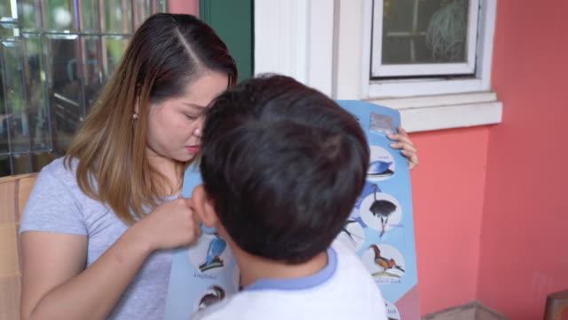 stockvideo's en b-roll-footage met aziatische moeder en vader leren dochter en zoon lees over de ontwikkeling - spelletjesavond