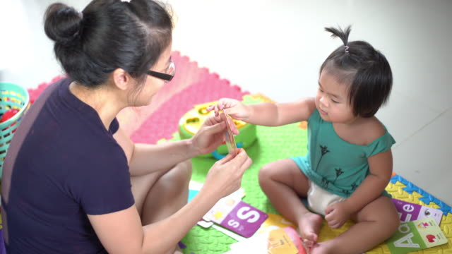asian mother and happy baby boy playing toy together on the floor in living room - baby boys stock videos & royalty-free footage