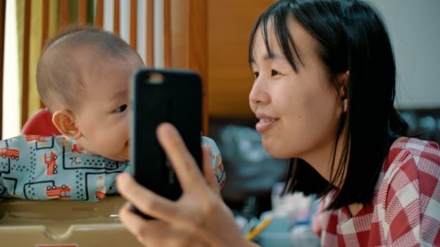 vídeos y material grabado en eventos de stock de madre asiática y bebé bebé feliz (6-11 meses) tomar selfie con el teléfono inteligente - 6 11 meses