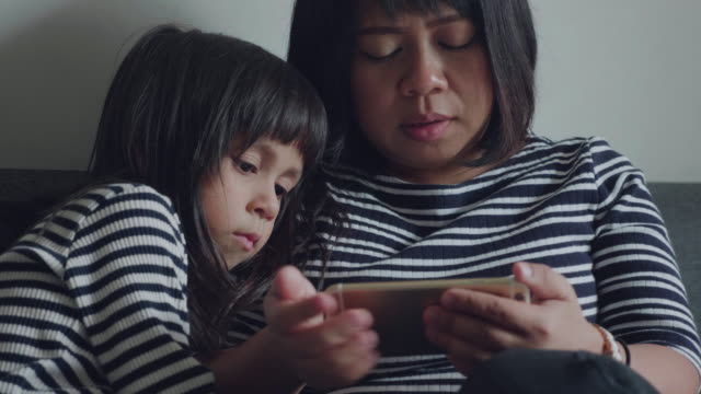 Asian Mother and Her Cute Daughter are Sitting On a Sofa in the Living Room.