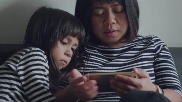 アジアの母と彼女のかわいい娘がリビング ルームにはソファに座っています。 - タイ人点の映像素材/bロール