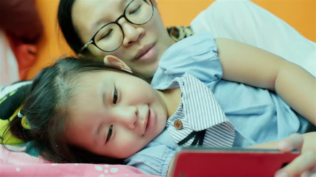 Asian Mother and her Daughter Using Smart Phone on the Bed