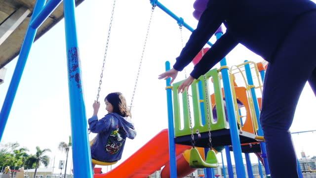 アジアの母と彼女の小さな娘がスローモーション、公園の遊び場のブランコに乗って - ブランコ点の映像素材/bロール
