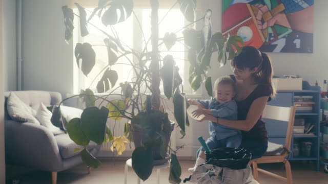 vídeos de stock e filmes b-roll de asian mother and her son caring for the home plant (slow motion) - vida simples