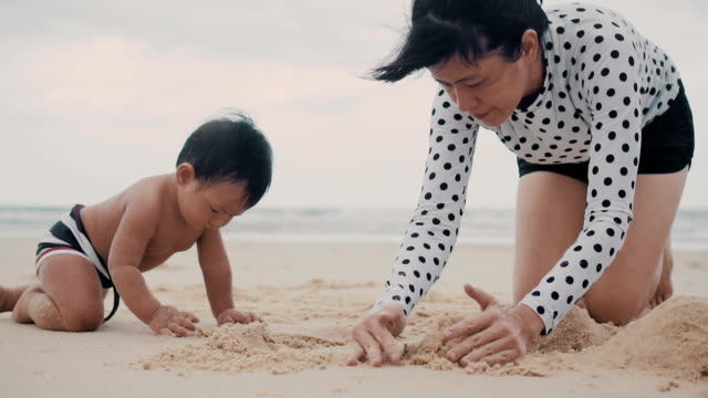 vídeos de stock, filmes e b-roll de asiática mãe e filho brincando com areia na praia - engatinhando