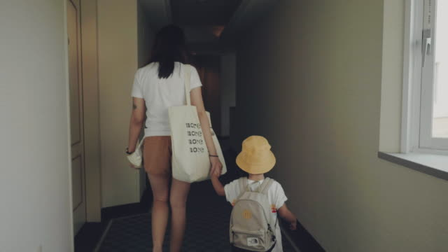 asian mother and her son pulling with suitcase at aisle in hotel. - corridor stock videos & royalty-free footage