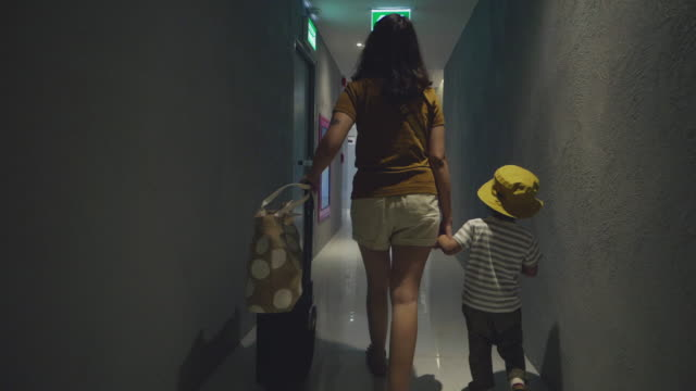 asian mother and her son pulling with suitcase at aisle in hotel. - hotel stock videos & royalty-free footage