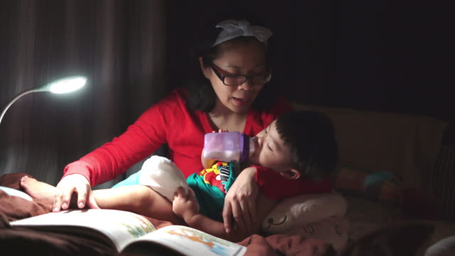 asian mother and her son reading a book on the bed at home - baby boys stock videos & royalty-free footage