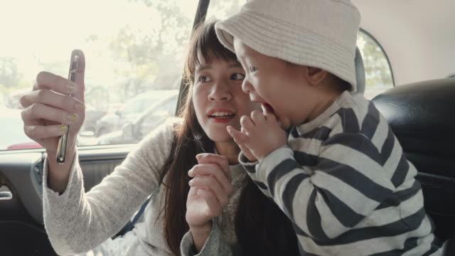 アジアの母と息子が彼女の車の座席後ろにスマート フォンで写真の。