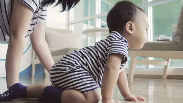 vídeos de stock e filmes b-roll de asian mother and little baby to crawl on the floor in the living room.4k - gatinhar
