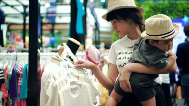 vidéos et rushes de une mère asiatique et petit garçon shopping au marché aux puces - brocante