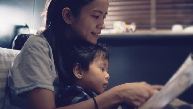 asian mother and little son reading in bed at night. - narrare storie video stock e b–roll