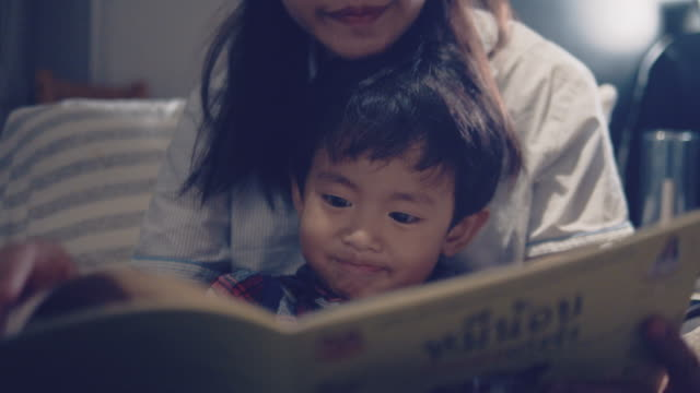 asian mother and little son reading in bed at night. - ora di andare a letto video stock e b–roll