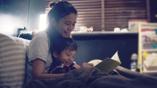 asian mother and little son reading in bed at night. - bedtime stock videos & royalty-free footage