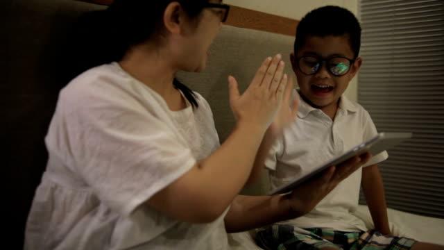 アジアの母と息子室内デジタル タブレットを使用している間手をたたく - ヘッドボード点の映像素材/bロール