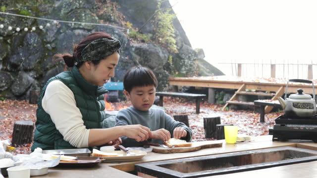 vídeos de stock e filmes b-roll de asian mother and son cooking outdoors - atividades ao ar livre
