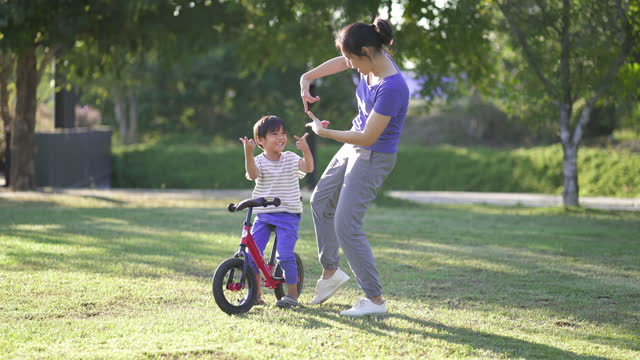 vídeos y material grabado en eventos de stock de madre e hijo asiáticos bailando juntos en el parque, al aire libre. - son