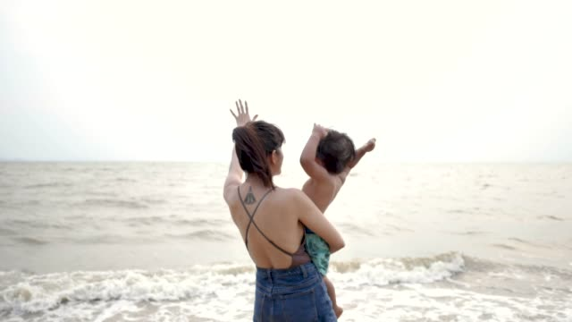 asian mother and son on the beach - tattoo stock videos & royalty-free footage