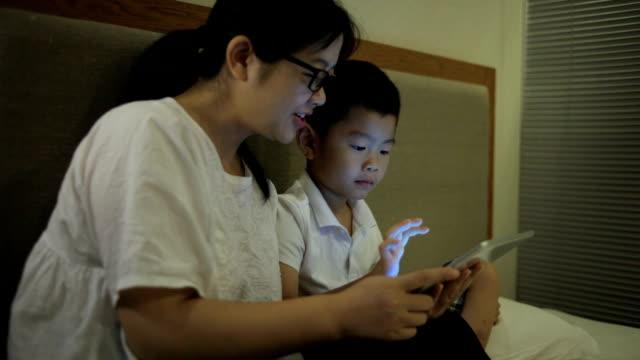 アジアの母と息子のデジタル タブレットの屋内での演奏 - ヘッドボード点の映像素材/bロール
