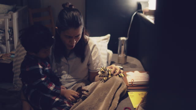 vídeos de stock e filmes b-roll de asian mother and son playing toys on the bed in night. - marionete