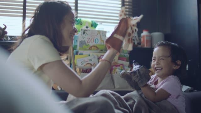 アジアの母と息子遊ぶトイズ - マリオネット点の映像素材/bロール