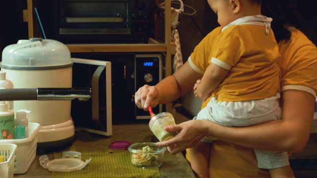 asian mother and son preparing baby food - microwave stock videos & royalty-free footage