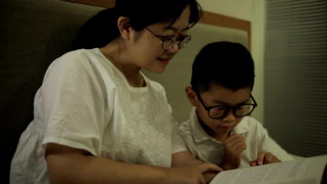 アジアの母と息子が室内で読書 - ヘッドボード点の映像素材/bロール