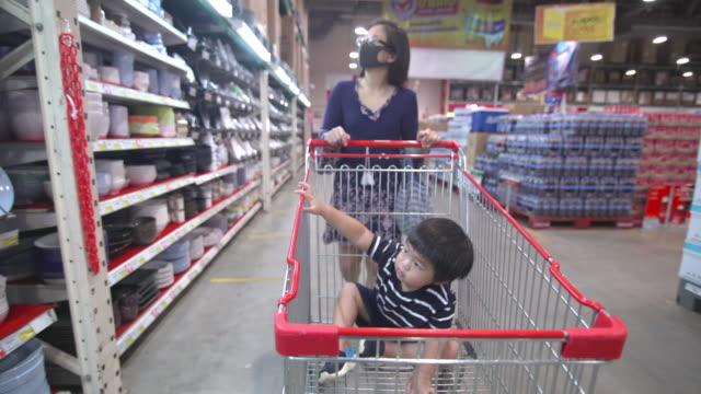 スーパーマーケットで買い物をするアジアの母と息子 - ニューノーマルコンセプト - メガストア点の映像素材/bロール