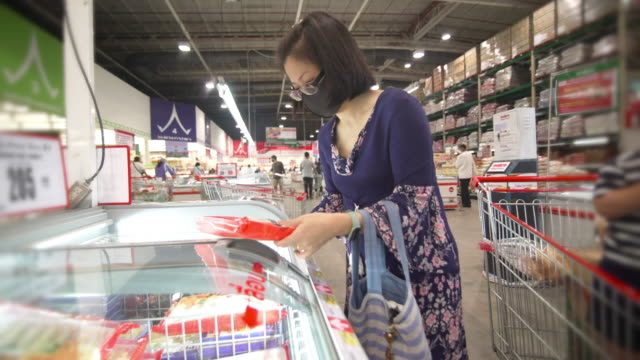asian mother and son shopping in a supermarket - new normal concept - cibi surgelati video stock e b–roll