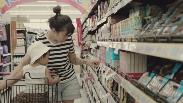 asian mother and son shopping in a supermarket - shelf stock videos and b-roll footage