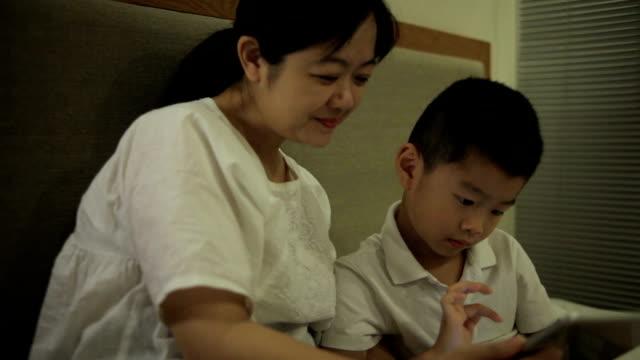 アジアの母と屋内でデジタル タブレットを使用しながら笑顔の息子 - ヘッドボード点の映像素材/bロール