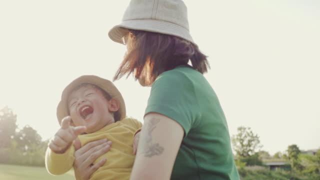 アジアの母と夕暮れの草原の回転の息子 - 肩に乗せる点の映像素材/bロール
