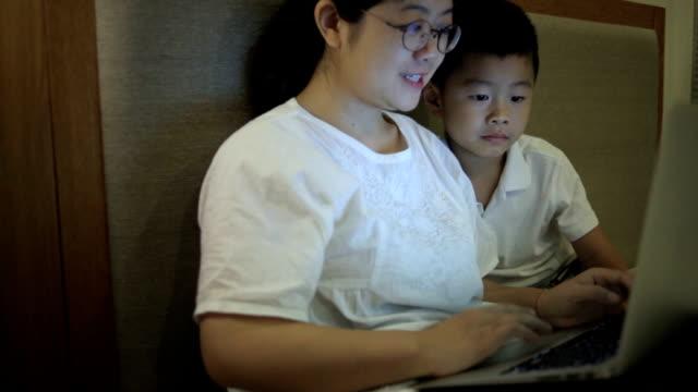 アジアの母とコンピューターを用いた屋内での息子 - ヘッドボード点の映像素材/bロール