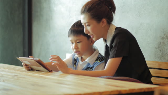 Asian mother and son using tablet computer